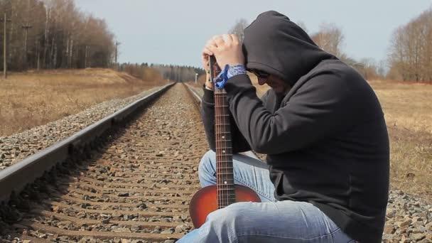 Stresující muž s kytarou na železnici