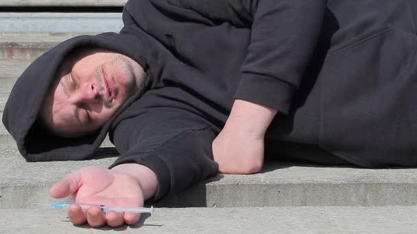 Drogové závislý člověk spí s injekční stříkačkou v ruce na venkovní