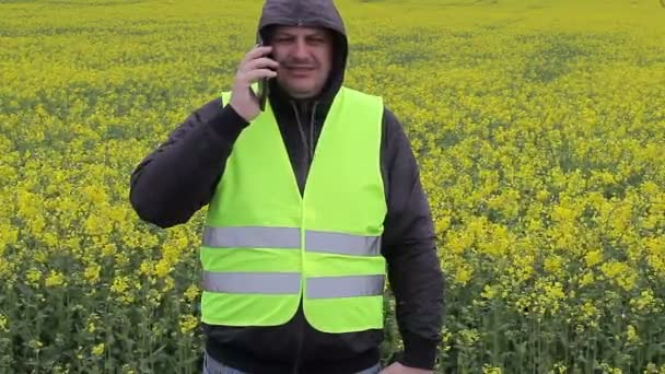 Farmer with cell phone near yellow rape field