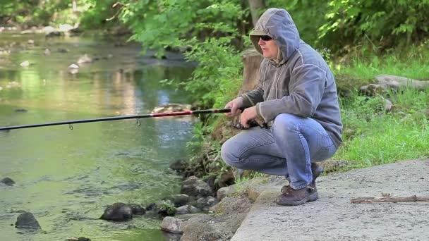 Muž s rybářským prutem poblíž řeky v létě