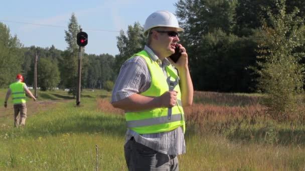 Železniční inženýr pomocí smartphone na železnici poblíž majáky signál