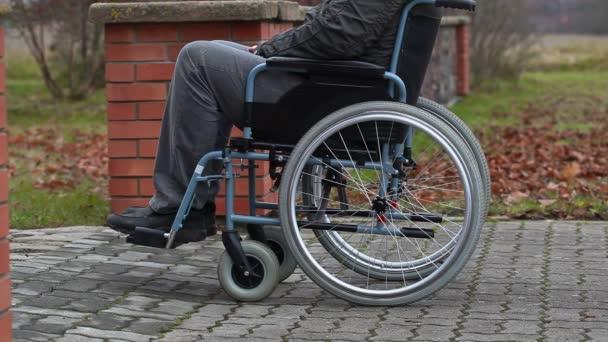 Disabled man in wheelchair on sidewalk