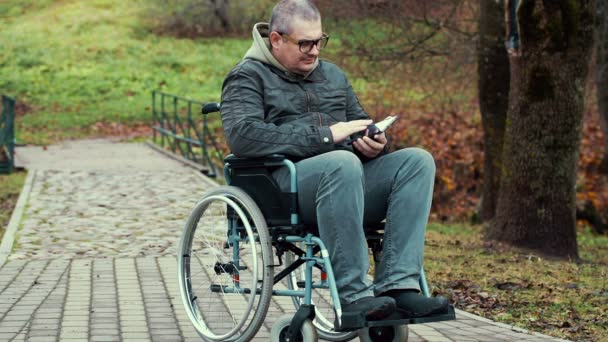 Disabled man using tablet PC in wheelchair