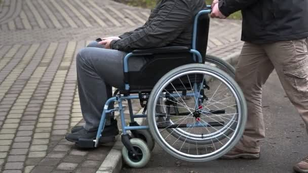 Assistant try pushing the wheelchair with disabled man on the pavement