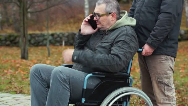 Disabled man talking on smartphone in wheelchair with assistant behind