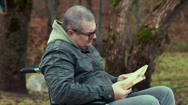 Zakázáno muž s knihou vozíku na venkovní v parku
