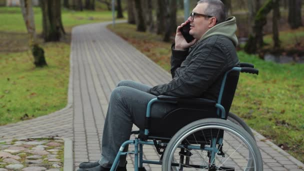 Disabled man in wheelchair on path talking on smartphone
