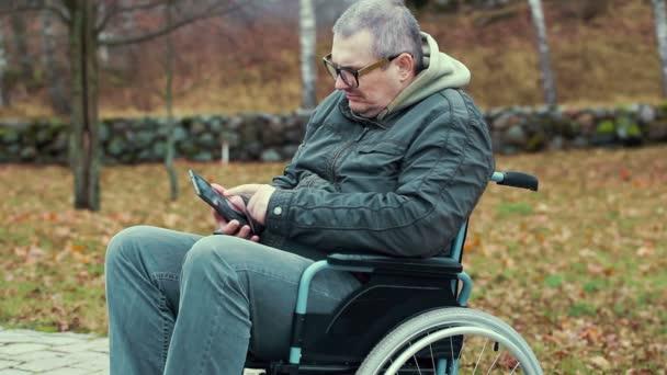 Zdravotně postižený muž na invalidním vozíku na cestu pomocí počítače tablet Pc