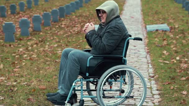 Lonely Disabled veteran in wheelchair at cemetery in autumn