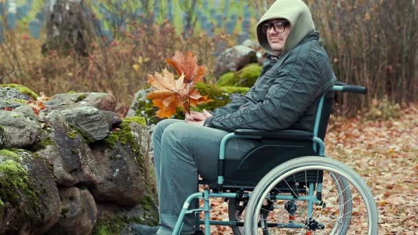 Disabled man with autumn leaves in wheelchair