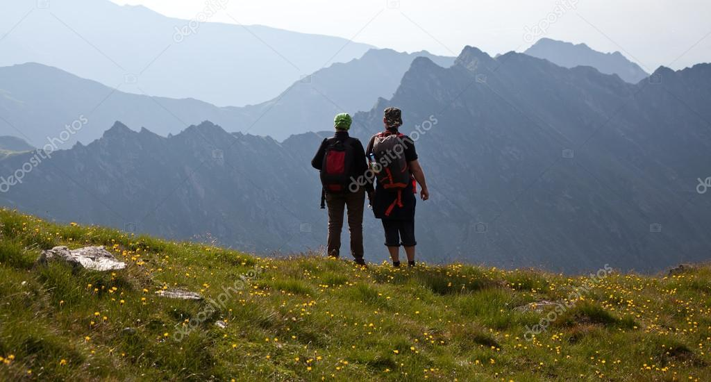 Couple of hikers admiring view and taking photographs of high mountains