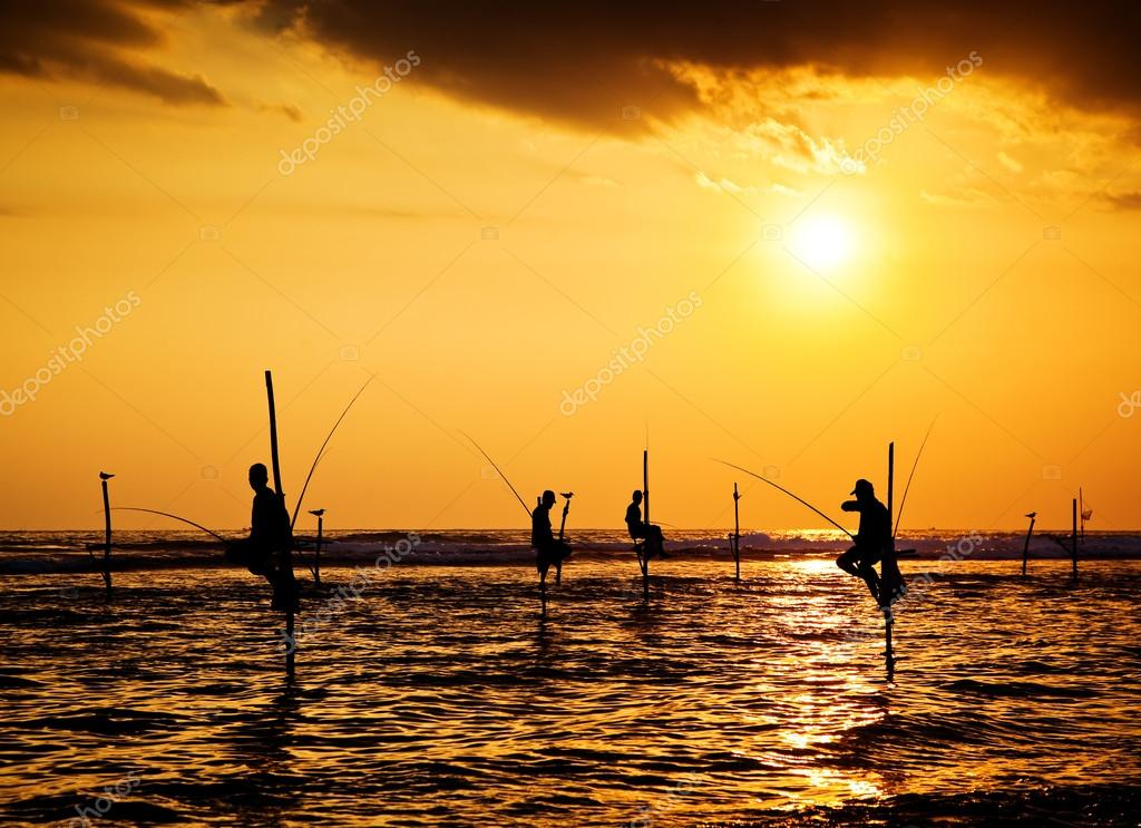 Silhouettes of the traditional stilt fishermen at the sunset nea