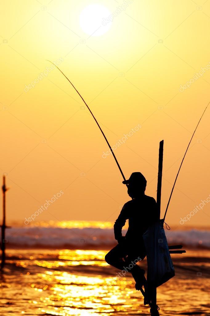 Silhouettes of the traditional stilt fishermen at sunset near Ga