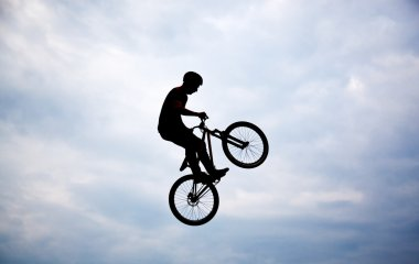 Silhouette of a man doing a jump with a bmx bike against sunset