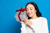 radostná žena v pleteném svetru drží dárková krabice izolované na modré
