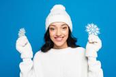 boldog nő kötött kalapban és kesztyűben kezében dekoratív hópelyhek elszigetelt kék