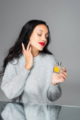happy woman with red lips applying perfume isolated on grey