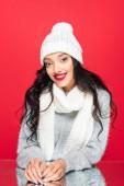radostná žena v klobouku a teplý šátek izolované na červené