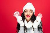 elégedett nő téli ruhában gazdaság dekoratív hópelyhek elszigetelt piros