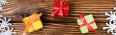 Draufsicht auf kleine Geschenkboxen in der Nähe von Schneeflocken auf Holzgrund, Banner