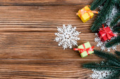 Top view of decorative snowflakes, little gift boxes and pine branch on wooden background, new year concept