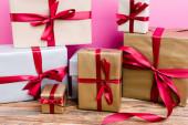 Zabalené dárkové krabice na růžovém pozadí, novoroční koncept