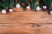 Draufsicht auf Tannenzweige, Kugeln und Anissterne auf braunem Holzgrund, Neujahrskonzept