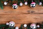 Flache Lage mit Weihnachtskugeln, Tannenzweigen und Anissternen auf braunem Holzgrund