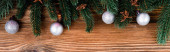 Top view of baubles, anise stars and pine branches on brown wooden background, banner