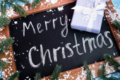 Close up view of chalkboard with merry christmas lettering near pine branches, little gift box and artificial snow