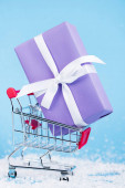 Close up view of little gift in shopping trolley on blue background, new year concept
