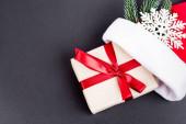 Top view ajándék mikulás kalap, dekoratív hópihe és fenyő ág fekete háttér, újév koncepció