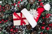 Ansicht von Fichtenzweigen mit Kunstschnee, Geschenkbox in der Nähe von Weihnachtsmütze und dekorativer Schneeflocke auf schwarzem Hintergrund