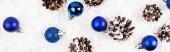 Horní pohled na borovicové šišky a vánoční ozdoby na bílém texturovaném pozadí, banner