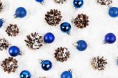 Lapos feküdt fenyőtobozok és karácsonyi baubles fehér texturált háttér