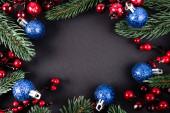 Top kilátás fenyő ágak, mesterséges bogyók és karácsonyi labdák fekete háttér