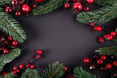 Photo Top view of red artificial berries and pine branches on black background, new year concept