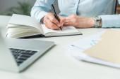 Vágott kilátás üzletasszony írás notebook, miközben ül a munkahelyen elmosódott előtérben