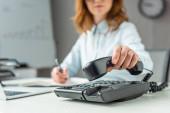 Ausgeschnittene Ansicht einer Geschäftsfrau, die ihr Mobiltelefon auf das Festnetztelefon legt, während sie am Arbeitsplatz auf verschwommenem Hintergrund sitzt