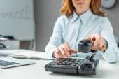 Ausgeschnittene Ansicht einer Geschäftsfrau mit Handywählnummer am Festnetztelefon am Arbeitsplatz auf verschwommenem Hintergrund