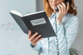 Ausgeschnittene Ansicht einer Geschäftsfrau, die ein Buch mit Schriftzug zum geistigen Eigentum hält, während sie am Festnetztelefon auf verschwommenem Hintergrund spricht