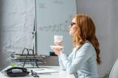 Oldalnézet üzletasszony csészealjjal és kávéscsészével néz félre, miközben ül a munkahelyen homályos háttér
