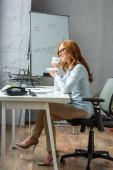 Voller Länge sitzt eine rothaarige Geschäftsfrau mit Kaffeetasse und Untertasse am Arbeitsplatz mit Flipchart im Hintergrund
