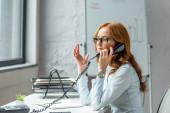 Fotografie Rothaarige Geschäftsfrau gestikuliert und telefoniert am Festnetztelefon, während sie am Arbeitsplatz vor verschwommenem Hintergrund sitzt