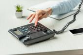 Fotografie Ausgeschnittene Ansicht einer Geschäftsfrau, die auf dem Festnetztelefon die Nummer wählt, auf dem Tisch mit Notizbuch und Anlage