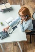 Blick auf rothaarige Geschäftsfrau, die am Arbeitsplatz am Festnetztelefon die Nummer wählt