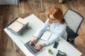 Fotografie Overhead-Ansicht einer rothaarigen Geschäftsfrau, die am Laptop tippt, während sie am Arbeitsplatz mit Geräten sitzt