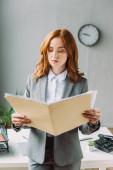 Seriöse Geschäftsfrau blickt auf Ordner mit Papierblättern, während sie in der Nähe ihres Arbeitsplatzes auf verschwommenem Hintergrund steht