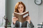 Fókuszált női ügyvéd olvasás könyv szerzői jog betűk közelében Themis figurine hivatalban homályos háttér