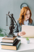 Themis figurine on pile of books on table with blurred female lawyer on background